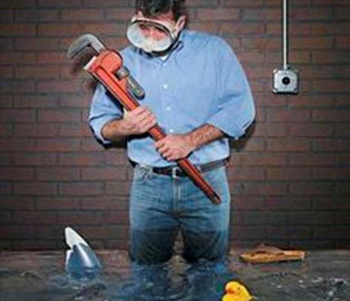 A guy standing in a flooded basement looking at a wrench in his hand